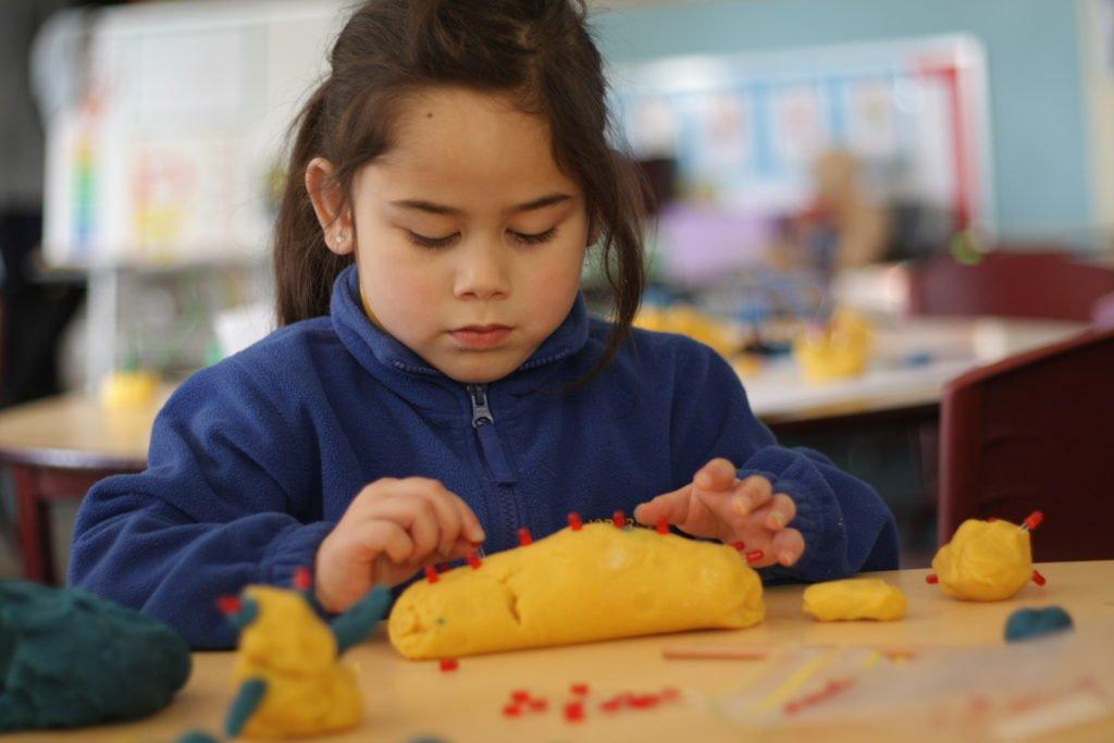girl making playdough caterpillar